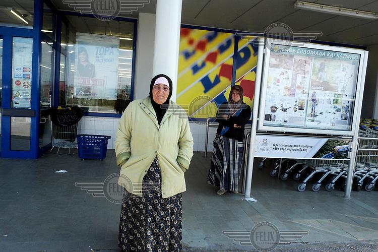 Two refugee women begging outside a Lidl Supermarket.