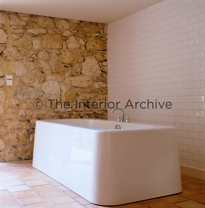 Old meets new in the master bedroom in a corner of which a freestanding bath by Marc Newson stands next to a stone wall