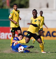 Jason Wright (10) of Jamaica steps through the tackle of Julio Ortiz (5) of Guatemala during the group stage of the CONCACAF Men's Under 17 Championship at Catherine Hall Stadium in Montego Bay, Jamaica. Jamaica defeated Guatemala, 1-0.