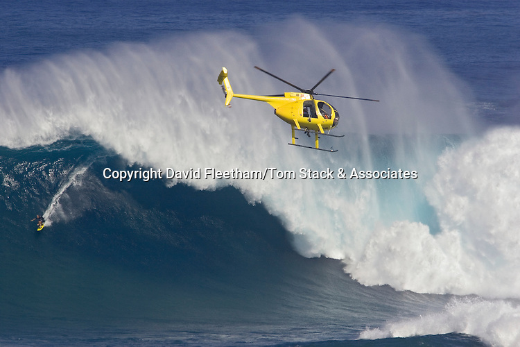 A helicopter filming a tow-in surfer at Peahi (Jaws) off Maui. Hawaii.