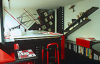 In Claude Parent's studio, the red, black and white theme is continued, while bookshelves hang at angles from the walls, echoing the geometric patterns