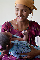 Laxmi Oli, 23, cradles her 3-day-old 2nd child in the Bardia District Hospital one hour's walk from her village in Bardia, Western Nepal, on 29th June 2012. Laxmi had her first child at 18. In Bardia, StC works with the district health office to build the capacity of female community health workers who are on the frontline of health service provision like ante-natal and post-natal care, and working together against child marriage and teenage pregnancy especially in rural areas. Photo by Suzanne Lee for Save The Children UK