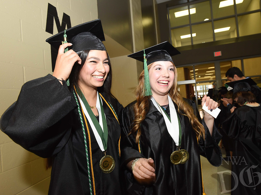 NWA Democrat-Gazette/FLIP PUTTHOFF <br /> Veronica Garcia-Carvajal (left) and Julia Kofler talk Saturday May 13 2017 with fellow graduates at the 27th annual Northwest Arkanas Community College commencement.