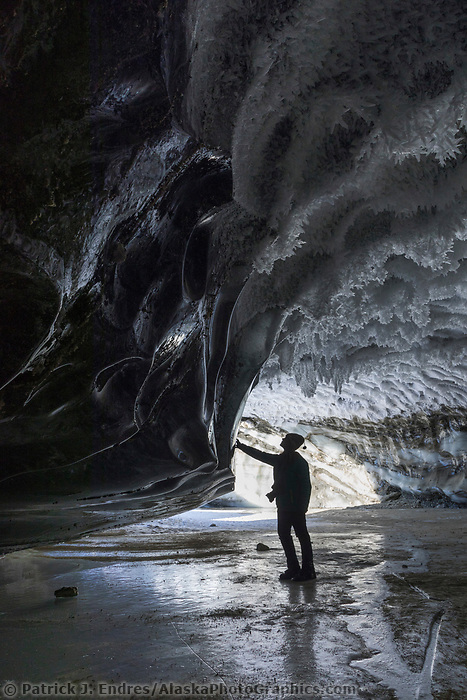Woman views ice crystals on the surface of a glacier ice cave in the Alaska Range mountians.