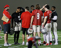 Ohio State fooball coaches, including co-offensive coordinator Tim Beck, middle, talk to the team's quarterbacks following the team's practice at the Woody Hayes Athletic Center on March 12, 2015. Quarterbacks J.T. Barrett, right, Cardale Jones, middle, and Braxton Miller, second from left, are expected to compete for the starting spot. (Adam Cairns / The Columbus Dispatch)