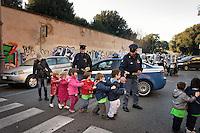 I bimbi di una scuola materna attraversano la strada aiutati da una Volante della Polizia di Stato che blocca il traffico.