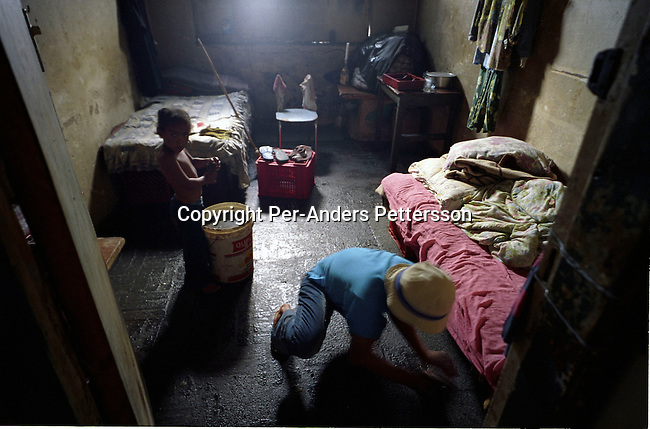 JOHANNESBURG, SOUTH AFRICA - FEBRUARY 16: An unidentified woman and her daughter clean their one-room flat on February 16, 2004 in downtown Johannesburg, South Africa. Hundreds of people have occupied Chancellor House, a building where Nelson Mandela had his lawyer?s office in 1952. The family lives in a room next to where Nelson Mandela used to work. They live in appalling conditions without running water, electricity or sanitation. Many rural South Africans come to Johannesburg to look for work and they face difficulties finding work and housing..(Photo: Per-Anders Pettersson/ iAfrika Photos.......