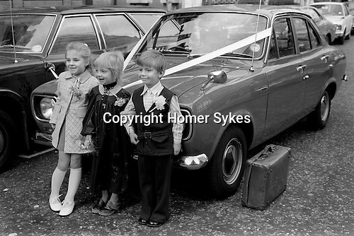 Children playing at just got married arm in arm having a photograph taken in front of 'going away' car. Old battered leather overnight suitcase waiting to be pit into car. London UK 1970s...My ref 14/424/, 1972,