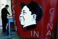 Claudio Sanò, artigiano del cuoio nel suo laboratorio con le borse con le immagini di Mao Tze Tung e una donna cinese..Claudio Sanò, leather craftsman in his workshop with the bags with pictures of Mao Tze Tung and a Chinese woman..