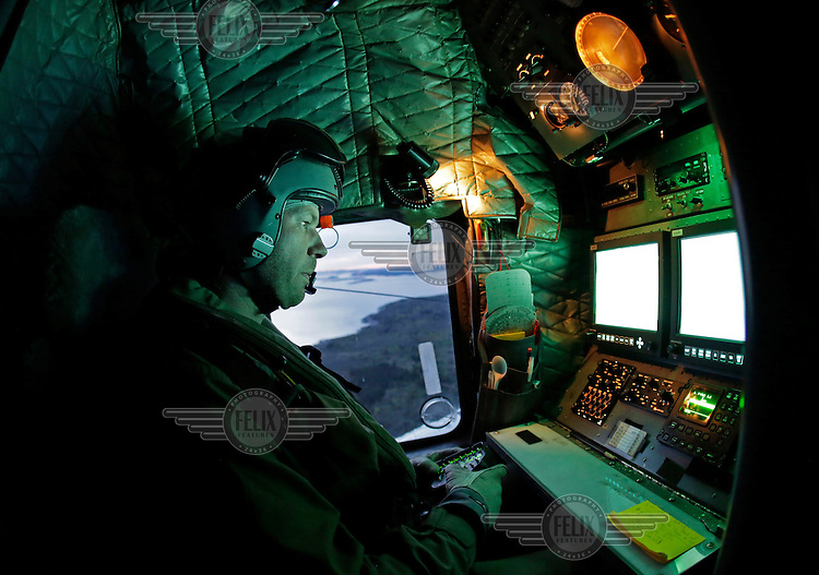 Systems operator Håvard Bakke monitoring radar and camera during a training mission. Crew from Norwegian Air Force 330 squadron, flying Westland Sea King helicopter. The core mission of the squadron is SAR (search and rescue), but they also fly HEMS (Helicopter Emergency Medical Service), complementing the civilian air ambulance service.<br /> This crew fly out of Rygge Air Station, Norway.