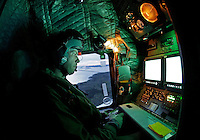 Systems operator Håvard Bakke monitoring radar and camera during a training mission. Crew from Norwegian Air Force 330 squadron, flying Westland Sea King helicopter. The core mission of the squadron is SAR (search and rescue), but they also fly HEMS (Helicopter Emergency Medical Service), complementing the civilian air ambulance service.<br />