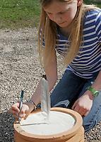 Kinder bauen eine Sonnenuhr, in einen mit Sand befüllten Blumentopf wurde eine Feder gesteckt, deren Schatten die Uhrzeit zeigen soll, nun werden Uhrzeiten am Rand aufgetragen