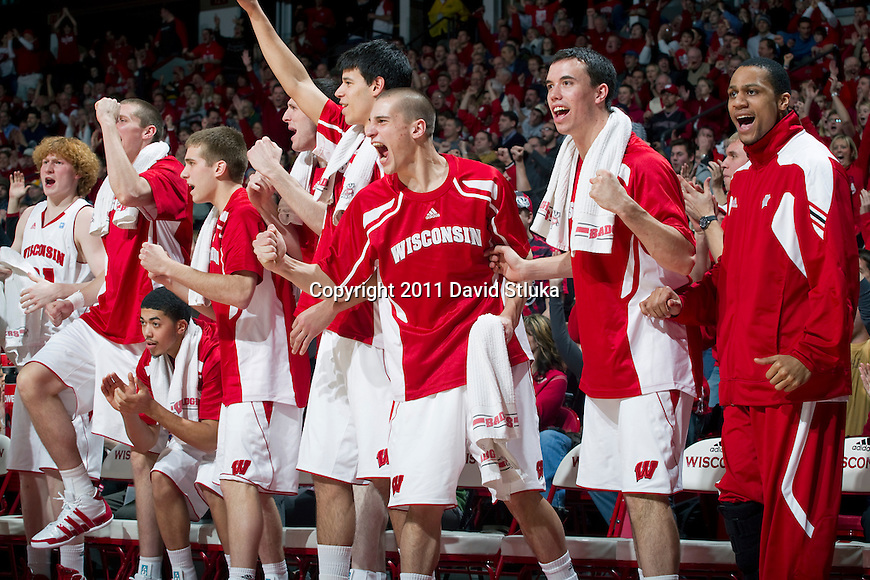 Wisconsin Badgers teammates cheer during a Big Ten Conference NCAA men's college basketball game against the Purdue Boilermakers on February 1, 2011 at the Kohl Center in Madison, Wisconsin. Wisconsin won 66-59. (Photo by David Stluka)