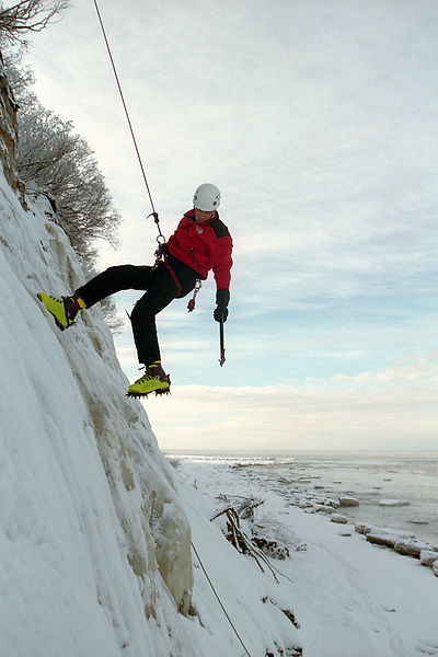 An ice climber works his way up a slab of ice hanging off a cliff on the bluff above Cook Inlet near Ninilchik, Alaska. The Kenai Peninsula is a playground of activity in the summer, but it is also an ideal location for winter sports and recreation.