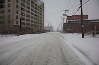 Detroit: paesaggio urbano. Una strada vuota e innevata tra i palazzi e i fili della corrente. Sulla carreggiata lievi segni di pneumatici sulla neve. All'orizzonte due comignoli fumanti.