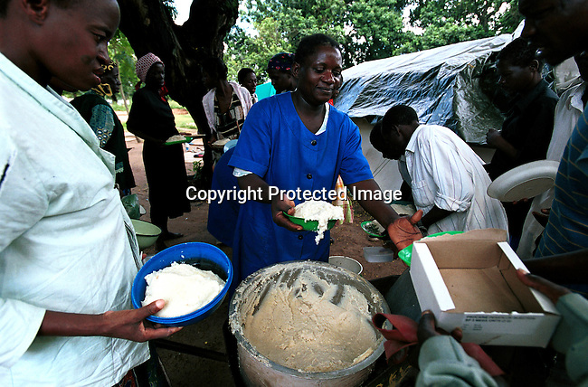 Hospital patients recieving food at a temporary hospital in Chakuelane, Mozambique. The hospital in Chokwe was destroyed by the severe flooding in the country in February-March 2000 and people fled to south to dry ground. Medicin Sans Frontiere (MSF) and other NGO:s delivered food and medical supplies to the town by helicopter..©Per-Anders Pettersson/iAfrika Photos