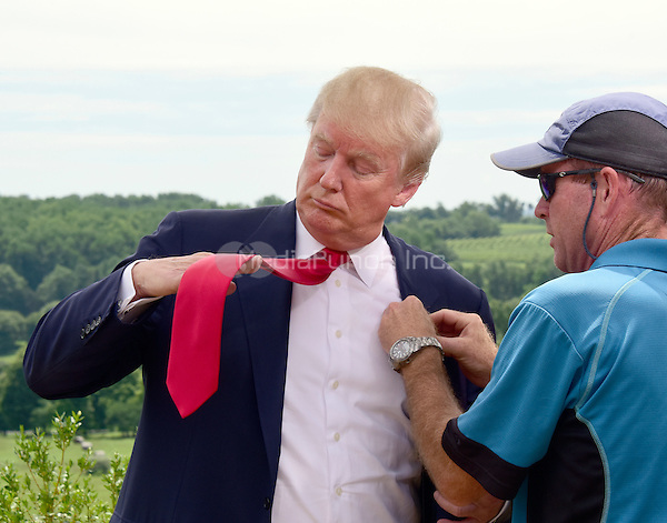 Donald Trump, a candidate for the 2016 Republican nomination for President of the United States, adjusts his tie as he prepares for an interview after appearing at the ribbon cutting for the Albemarle Estate at the Trump Winery in Charlottesville, Virginia on Tuesday, July 14, 2015. <br /> Credit: Ron Sachs / CNP/MediaPunch<br /> <br /> (RESTRICTION: NO New York or New Jersey Newspapers or newspapers within a 75 mile radius of New York City)
