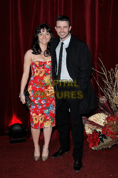 GUESTS .Attending The British Soap Awards 2010, The London Television Centre, London, England, UK, 8th May 2010 .arrivals full length strapless red floral print dress suit tie black .CAP/CAN.©Can Nguyen/Capital Pictures.