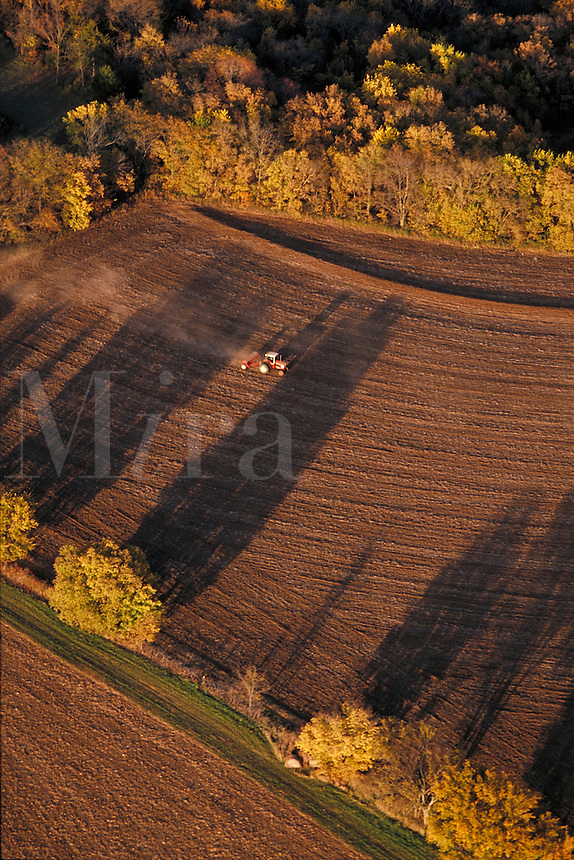 Aerial of a tractor cultivating a field.