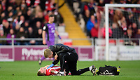 Lincoln City's Harry Anderson receives treatment for an injury from Lincoln City's head of sports science and medicine Mike Hine<br /> <br /> Photographer Chris Vaughan/CameraSport<br /> <br /> The EFL Sky Bet League Two - Lincoln City v Port Vale - Tuesday 1st January 2019 - Sincil Bank - Lincoln<br /> <br /> World Copyright &copy; 2019 CameraSport. All rights reserved. 43 Linden Ave. Countesthorpe. Leicester. England. LE8 5PG - Tel: +44 (0) 116 277 4147 - admin@camerasport.com - www.camerasport.com