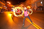 Fire twirlers march in Sutter Creek's annual Parade of Lights Christmas parade downtown on a rainy night in the  Mother Lode of Calif.