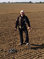 BNPS.co.uk (01202 558833)<br /> Pic: DNW/BNPS<br /> <br /> He's in the money - Detectorist Don Crawley from Suffolk.<br /> <br /> A builder is celebrating today after an enormous hoard of silver coins he unearthed sold for £90,000.<br /> <br /> Don Crawley was searching farmland with his metal detector when he stumbled upon the buried treasure.<br /> <br /> He dug up 99 silver coins - 81 pennies and 18 cut halfpennies - all dating back to Anglo Saxon England and the reign of King Ethelred II from 978-1016AD.<br /> <br /> The discovery was made on farmland in Suffolk and research has established that the site used to be the grounds of a long-forgotten Saxon church. Specialists even later uncovered the remains of human bones from the site dating back over 1,000 years.<br /> <br /> Don's hoard went under the hammer with London auctioneers Dix Noonan Webb - with the coins substantially out-performing their £50,000 pre-sale estimate.