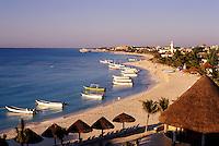 Mexico, Playa del Carmen. Beach scene with palapas, fishing boats and Caribbean Sea. Also known as the Mayan Rivera or Mayan Coast