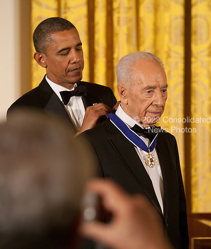 United States President Barack Obama awards the Presidential Medal of Freedom to President Shimon Peres of Israel during a dinner in his honor in the East Room of the White House in Washington, D.C. on Wednesday, June 13, 2012..Credit: Martin Simon / Pool via CNP