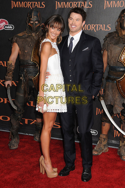 "Sharni Vinson and Kellan Lutz.""Immortals"" World Premiere held at Nokia Theatre LA Live, Los Angeles, California, USA..November 7th, 2011.full length white shirt blue suit waistcoat side hand in pocket white dress perforated couple silver clutch bag beige nude shoes .CAP/ADM/BP.©Byron Purvis/AdMedia/Capital Pictures."