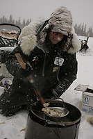 Ed Iten cooks fish for his dogs as he takes a break at the Nikolai checkpoint