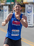 Rob Lugg, the men's marathon winner, jumps in the air as he crosses the finish line in the Downtown River Run on Sunday, April 30, 2017 in Reno, Nevada.
