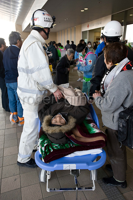 An elderly patient awaits to receives treatment in a makeshift ward set up in the foyer of the Ishinomaki Red Cross Hospital in Ishinomaki, Japan on 13 March, 2011.  Photographer: Robert Gilhooly