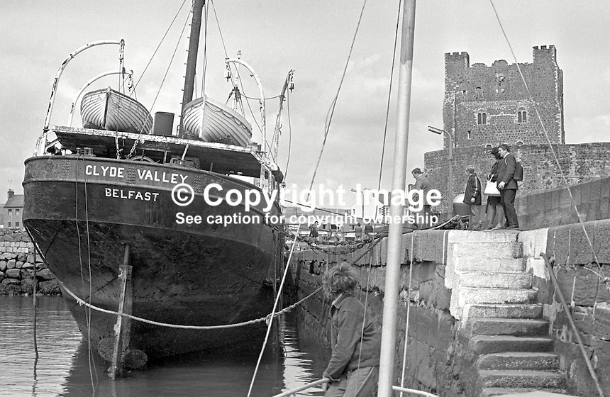 Clyde Valley, the former UVF gun-running ship, which is to be towed to a breaker's yard in England, UK. It is seen berthed in the Harbour at Carrickfergus, Co Antrim, N Ireland. Carrickfergus Castle is in the background. 197407300414a <br />