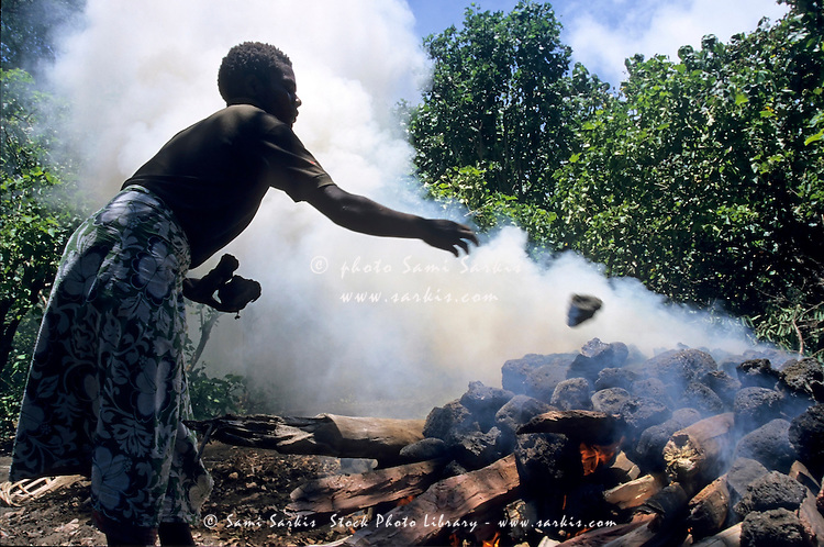 Woman throwing stones on a smoky fire, Sulphur Bay Village, Ipekel Ipeukel, Tanna Island, Vanuatu.