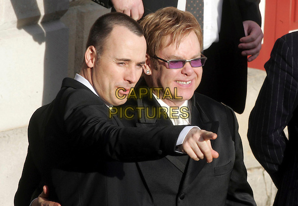 DAVID FURNISH & ELTON JOHN.Sir Elton John & David Furnish - civil partnership ceremony (wedding) at Guildhall, Windsor, Berkshire, England..December 21st, 2005.Ref: FIN.half length couple pointing gesture tinted glasses.www.capitalpictures.com.sales@capitalpictures.com.© Capital Pictures.