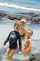 A young local girl and boy play in a tidal pool while the boy's mother supervises, Puako, South Kohala, Big Island.