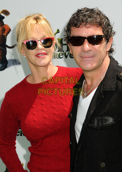 "MELANIE GRIFFITH & ANTONIO BANDERAS .Attending the ""Shrek Forever After"" Los Angeles Film Premiere held at the Gibson Amphitheatre, Universal City, California, USA, 16th May 2010..arrivals half length red jumper cable knit sweater ray bans sunglasses wayfarers black jacket white t-shirt married couple husband wife necklace .CAP/ADM/BP.©Byron Purvis/AdMedia/Capital Pictures."