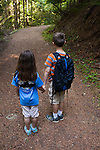 An eight year old boy and six year old girl (brother and sister) hold hands while hiking along a trail in Bonner County, Idaho