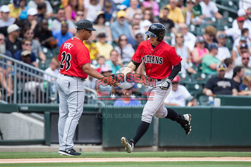 Austin Meadows (19) of the Indianapolis Indians slaps hands with third base coach Miguel Perez (28) as he rounds the bases after hitting a home run against the Charlotte Knights at BB&T BallPark on June 19, 2016 in Charlotte, North Carolina.  The Indians defeated the Knights 6-3.  (Brian Westerholt/Four Seam Images)