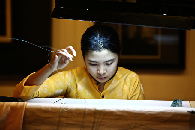 A young woman dressed in a traditional ao dai works on a piece of hand-embroidered silk at a workshop in Hoi An, Vietnam. The city is famous for its clothes shops. Tailored suits and dresses can be purchased cheaply and made in as little as a day, but workshops such as this one are devoted to more traditional arts. April 22, 2012.