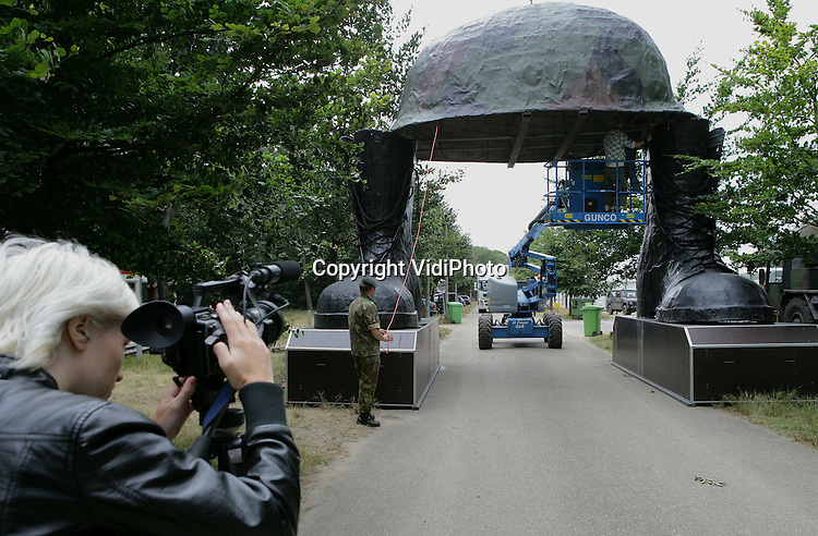 Foto: VidiPhoto..NIJMEGEN - Op het militair kamp Heumensoord bij Nijmegen zijn maandagmiddag de reuzenhelm en laarzen geplaatst die de entree van het kamp vormen. Op Heumensoord verblijven tijdens de Vierdaagse van Nijmegen, het grootste wandelevenement ter wereld, zo'n 5300 militairen van 17 nationaliteiten. Voor het grootste wandelevenement ter wereld hebben zich ongeveer 45.000 wandelaars ingeschreven. De helm en laarzen wegen meer dan een ton, ondanks dat het materiaal van kunststof is.