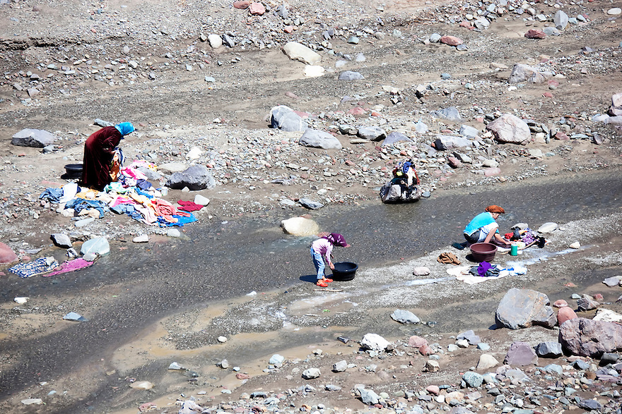 Women and child washing cloths in the river, Morocco.