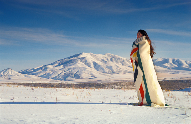 Lemhi-Shoshone woman and Sacagawea descendant wrapped in a candy striped wool trade blanket, historically a trade item from the Hudson Bay Trading Company, stands on a snowy winter landscape on the Fort Hall Indian Reservation; Idaho