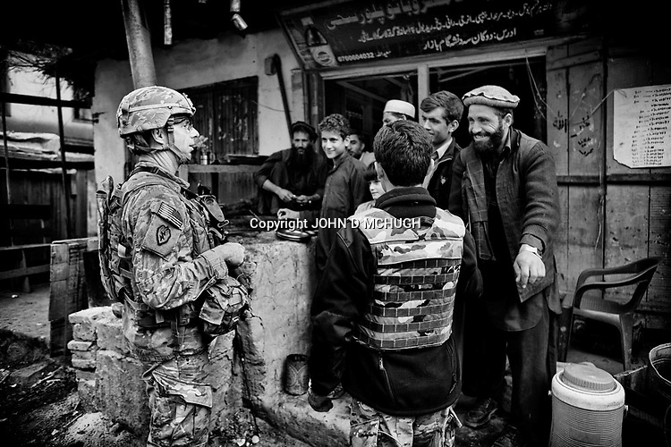 US Army Lieutenent Colonel Dan Wilson, Battalion Commander of 2/27 Infantry, 25th Infantry Division, chats with local Afghans in Nishigam village, Kunar Province, 05 December 2011.  (John D McHugh)