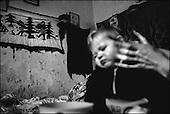 Katarzynowo, Northern Poland, December 2005<br /> The faces of Polish poverty<br /> Waldemar and Agnieszka Srednicki have 7 children. He works at the public street projects earning 180 Euros a month. She's unemployed but gets only a small benefit of 120 Euros for their children. Katarzynowo in northern Poland is an ex-collective farm village forgotten by the state, where people have no other choice but to vegetate in extreme poverty<br /> ( &copy; Filip Cwik / Napo Images for Newsweek Polska)<br /> <br /> Katarzynowo k. Elku 29 listopad 2005 Polska<br /> Oblicza biedy w Polsce<br /> Waldemar i Agnieszka Sredniccy maja siedmioro dzieci. On pracuje przy robotach publicznych, uklada plytki chodnikowe. Zarabia 600 zl z czego 180 wydaje na dojazy do Elku. Ona pobiera  zasilek 410 zl i od czasu do czasu 102 zl. W 1992 wyprowadzili sie z Elku z braku pracy na wies do domu ojca. dzieci Samanta, Sandra, Robert, Michal, Rafal, Daniel, Kazimierz. Katarzynowo wies w warminsko - mazurskim 20 km od Elku. Typowa po PGR-owska wies zapomniana przez panstwo. Wiekszosc mieszkancow jest bez pracy. Okoliczne wysypisko smieci jest jedynym zrodlem dochodu wiekszosci rodzin. Zbieraja puszki, gume i wszystko co ma jakakolwiek wartosc.<br /> <br /> Wiekszosc Polakow niemal / 85% / z trudem radzi sobie z przezyciem od pierwszego do pierwszego. Ponad polowa / 52,5% / zalega ponad trzy miesiace z czynszem. Tyle samo osob, aby poprawic swoja sytuacje materialna radykalnie ogranicza wydatki. W beznadziejnej sytuacji jest ludnosc wiejska gdzie 18,5% zyje w skrajnej nedzy. W 1991 roku rzad polski zlikwidowal Panstwowe Gospodarstwa Rolne ktore od II Wojny Swiatowej byly miejscem pracy dla ponad 2 mln rolnikow glownie na ziemiach odzyskanych. Ci ludzie i ich rodziny nie odnalezli sie w nowej rzeczywistosci<br /> ( &copy; Filip Cwik / Napo Images dla Newsweek Polska)