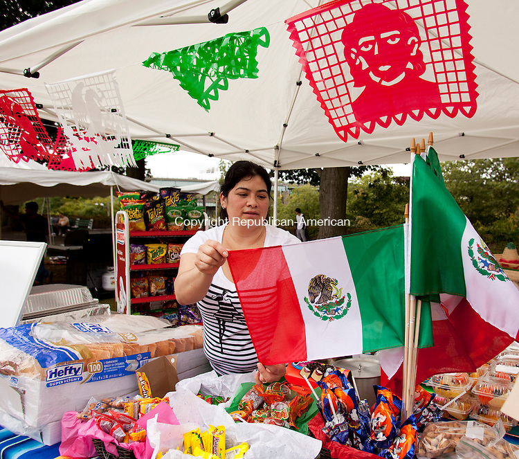 WATERBURY, CT-21 September 2013-092113BF09- Lidia Mendoza from Waterbury arranges Mexican flags for sale in her booth during the first ever Festival Mexicano held Saturday at Library Park in Waterbury. Mendoza, a native of Oaxaca, Mexico, runs El Mexicano, a Mexican Grocery store on South Main Street in Waterbury.Bob Falcetti Republican-American
