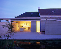 Exterior view at dusk of the concrete terrace of the converted cowshed to the rear of this traditional Welsh cottage