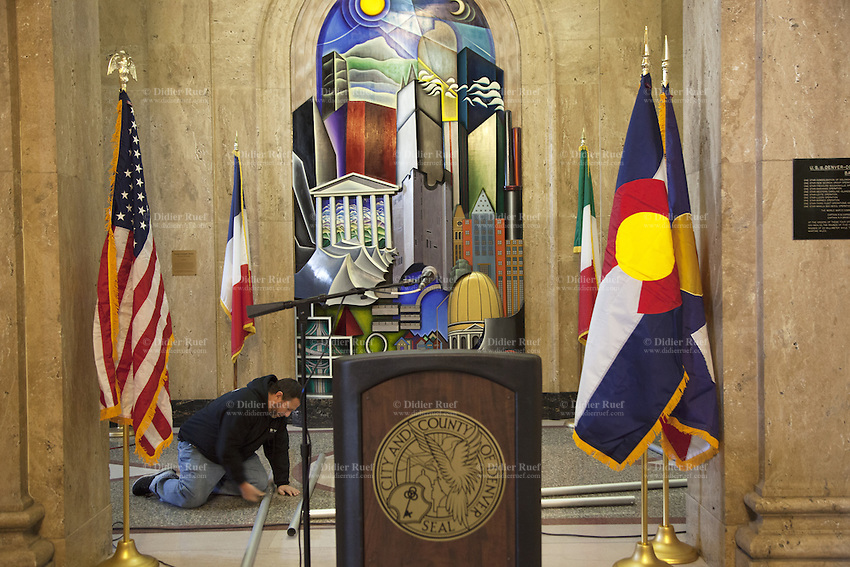 "USA. Colorado state. Denver. Worker on his knees inside the building of City and County of Denver. Four flags, Usa, Denver, France and Italy. A microphone and a stand used for media conferences. The flag of the City and County of Denver, Colorado, was designed by North Denver high school student, Margaret Overbeck, and adopted in 1926. A zigzag white stripe horizontally separates a blue field above, in which is centered a yellow circle, from a red field below, together forming a stylized depiction of the sun in a blue sky above snow-capped mountains. The color yellow symbolizes gold in the state's hills, and red the colored earth to which the word Colorado refers. The circle's centered position symbolizes Denver's central location within the state. The white zigzag symbolizes Colorado's Native American heritage. The national flag of the United States of America, often referred to as the American flag, consists of thirteen equal horizontal stripes of red (top and bottom) alternating with white, with a blue rectangle in the canton (referred to specifically as the ""union"") bearing fifty small, white, five-pointed stars arranged in nine offset horizontal rows of six stars (top and bottom) alternating with rows of five stars. 18.12.2014 © 2014 Didier Ruef"