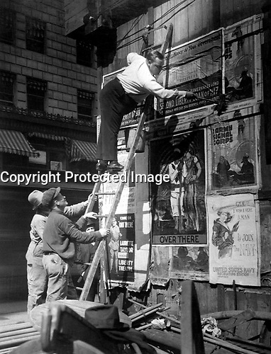 Second Liberty Loan, Oct. 1917.  Fattie Arbuckle, the movie star, putting up a Liberty Loan poster at Times Square, New York.  Paul Thompson. (War Dept.)<br />Exact Date Shot Unknown<br />NARA FILE #:  165-WW-232B-13<br />WAR & CONFLICT BOOK #:  519
