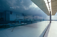 The glass walls of the living area reflect the rolling grey clouds of the dramatic weather conditions